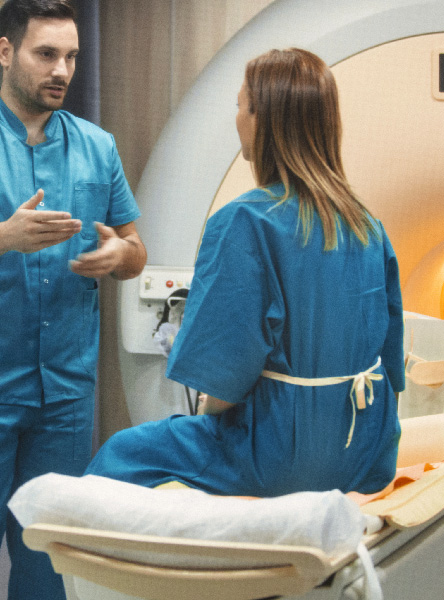 A woman preparing to go into an MRI machine while a nurse explains